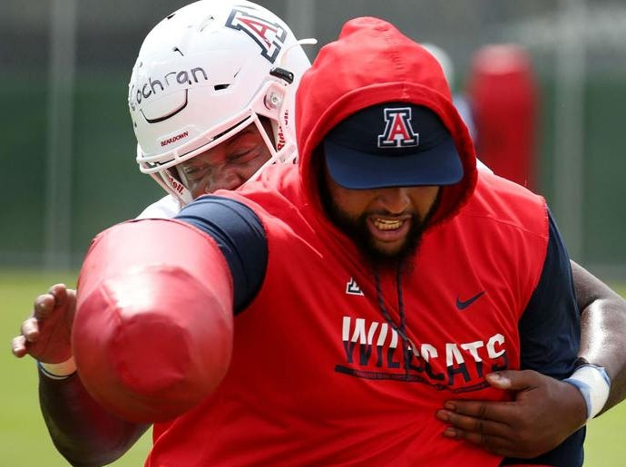 Graduate assistant Tevin Hood takes one for the team as Arizona Wildcats defensive lineman Jalen Cochran lunges around him.