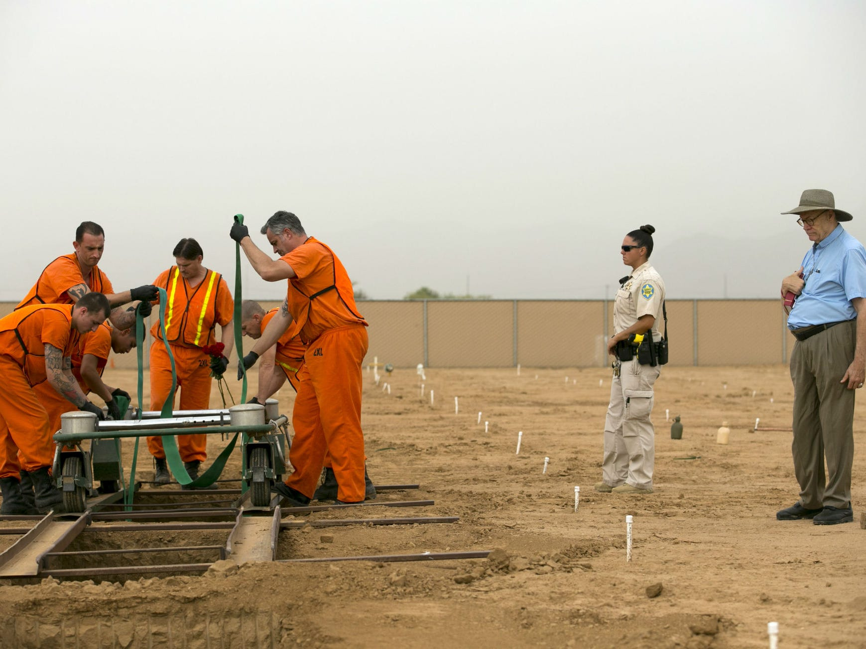 Maricopa County jail inmates assist with the burial of an indigent individual as Chaplain Thomas Chapman, the Maricopa County coordinator for indigent burials, oversees the burials while a Maricopa County Corrections Officer D. Prazak keeps a watchful eye at the White Tanks Cemetery in Litchfield Park on Aug. 9, 2018.