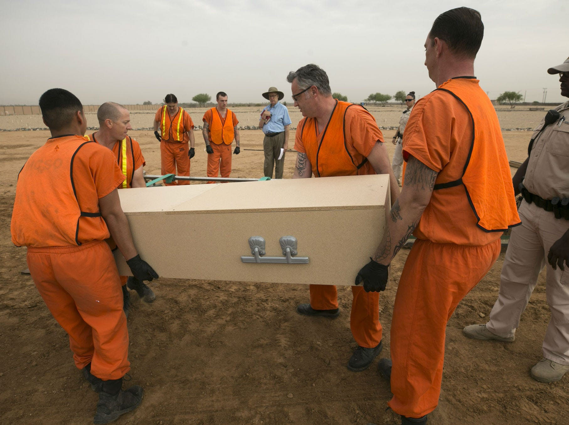 Maricopa County jail inmates assist as Chaplain Thomas Chapman, (background) the Maricopa County coordinator for indigent burials, oversees the burial while a Maricopa County corrections officer keeps a watchful eye at the White Tanks Cemetery in Litchfield Park on Aug. 9, 2018.