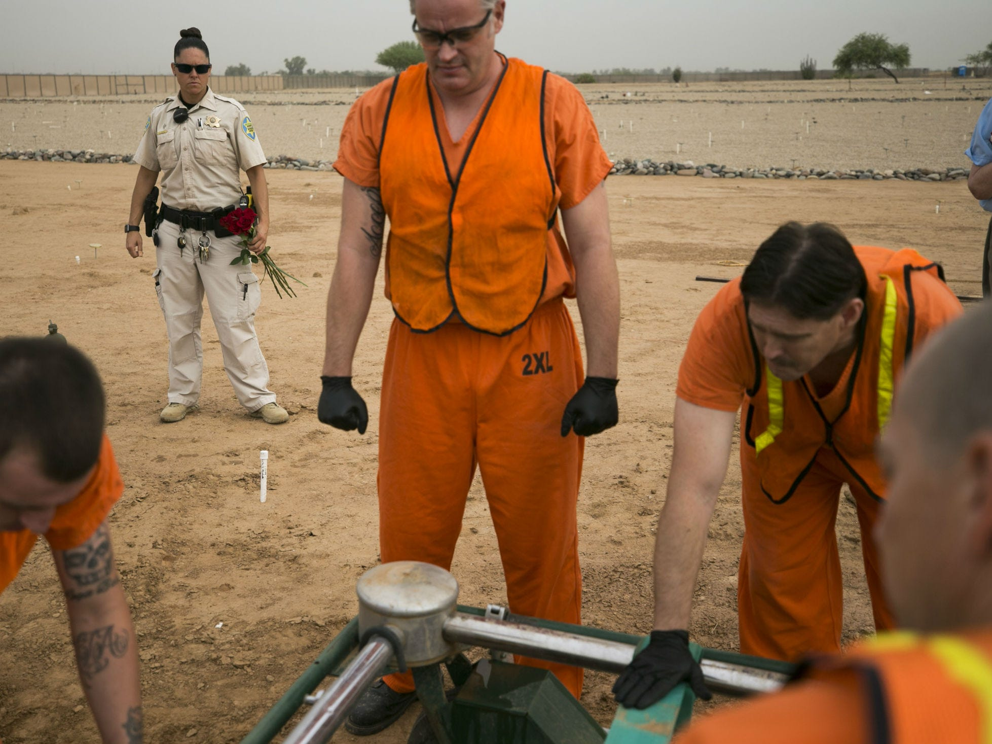 Maricopa County jail inmates assist with the burial of an indigent individual as Maricopa County Corrections Officer D. Prazak keeps a watchful eye at the White Tanks Cemetery in Litchfield Park on Aug. 9, 2018.