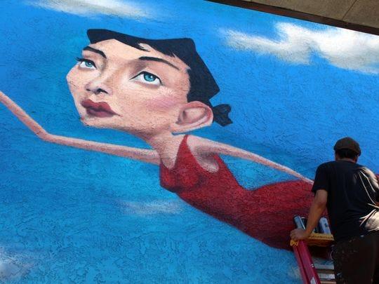 Tato Caraveo dijo que se especializa en surrealismo y realismo en sus murales. Este mural de una mujer en el cielo se exhibirá en una pared frontal en el complejo de apartamentos Park View en Tempe.