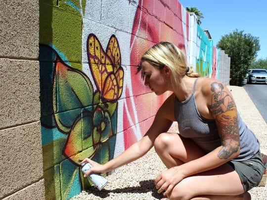 Nyla Lee, de 21 años, es relativamente nueva en la comunidad muralista de Phoenix, pero muchos de sus murales ya se pueden encontrar en el centro de la ciudad. Aquí, ella trabaja en una pieza mural más pequeña para un patio trasero.
