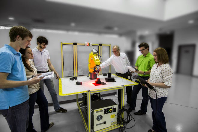 Students practice with a robot at FANUC America's headquarters in Rochester Hills, Michigan. FANUC America is now offering training courses as part of the Great Lakes Advanced Manufacturing Collaboration through Croswell-Lexington Community Schools.