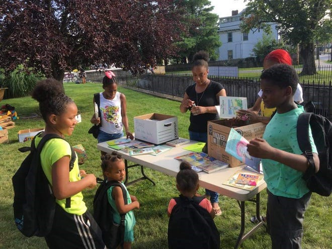 Brooksie Brown (center, in black T-shirt), director of the women's program at Rebuilding Our Children and Community, and volunteer Kenya Humes help children select books to bring home during the nonprofit's back-to-school giveaway last year.