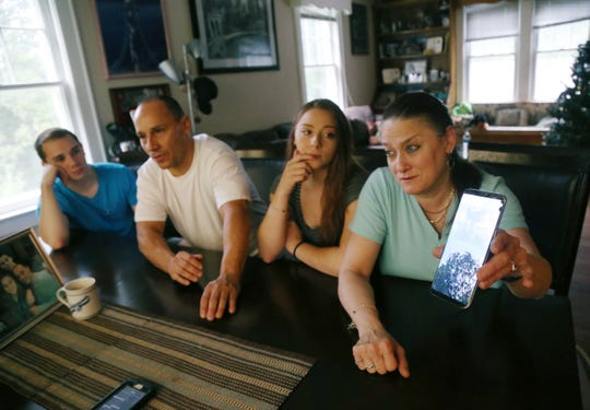 The Colon family, from left, Erick, Fred, Jillian and ToniAnn at their home in the Town of Poughkeepsie on August 9, 2018. ToniAnn shows a photo that was taken around the time their son, Dillon was in a fatal car accident in 2017. The cloud formation resembles an angel, which they believe was a sign of what tragedy befell their son.