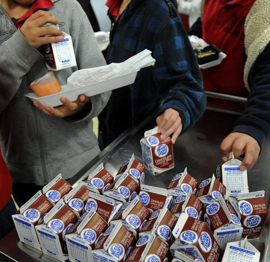 Students get chocolate milk during lunch at school in this USA Today Network file photo.