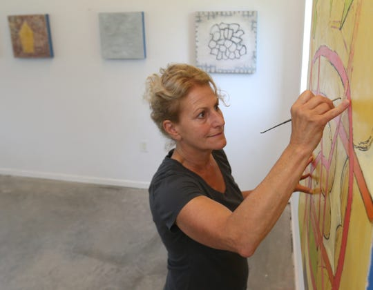 Donise English works on a painting in her studio in the Town of Poughkeepsie on August 8, 2018.