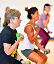 Roxanne Bell, front, of Springettsbury Township, and Deb Weaver, of York Township, use weights during Body Sculpt class at Body Rhythms Life Fitness in Springettsbury Township, Wednesday, Aug. 8, 2018. In honor of their seventh anniversary, the studio, located at 1240 Greensprings Dr., will be offering free classes all day Saturday, Aug. 11. Dawn J. Sagert