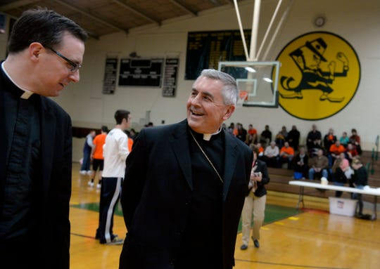 """Father Jonathan Sawicki, dean of the York Deanery, and Bishop Ronald Gainer of the Harrisburg Diocese enter the York Catholic High School gym for the """"Battle of the Buildings"""" event on Saturday, Jan. 24, 2015. The high school hosted the inaugural """"Battle of the Buildings"""" -- a friendly competition between teams representing each of the six schools in the York Deanery -- to kick off Catholic Schools Week."""