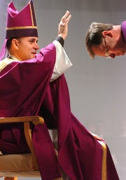 Diocese of Harrisburg Bishop Kevin Rhoades, left, sends Father William Cawley, the head of the religion department at York Catholic High School, to read the good news of the gospel in this 2005 file photo.
