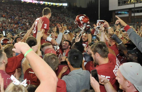 Washington State  quarterback Tyler Hilinski is lifted up by his teammates after a 47-44 win over Boise State.