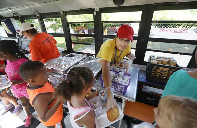 Jennifer Rosario, right, with food services at the Gates Chili School District, serves a hot lunch including hash browns, to kids at Memorial Park inside the new Spartan East Food Bus in Gates Thursday, Aug. 9, 2018.  The bus is the creation of the Gates Chili School District.