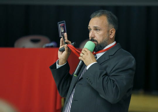 David Inzana, director of security for the Hilton School District, mentions ID passes as he speaks during a public meeting on the possibility of Hilton schools potentially getting armed guards, at Merton Williams Middle School.