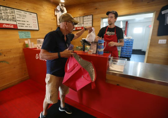 Tom LaMartina, a Grubhub driver, picks up an order from Karsten Brooks at Playhouse/ Swillburger in Rochester in 2018. The store's Grubhub tablet showed another driver coming.
