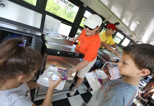 Donna Bailey, center, with bus transportation at the Gates Chili School District, serves a hot lunch to kids at Memorial Park inside the new Spartan East Food Bus.