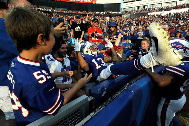 Buffalo Bills wide receiver Kelvin Benjamin, center, dives into the first row of the stands after catching a touchdown pass from quarterback Nathan Peterman during the first half of an NFL football game against the Carolina Panthers, Thursday, Aug. 9, 2018, in Orchard Park, N.Y. (AP Photo/Adrian Kraus)