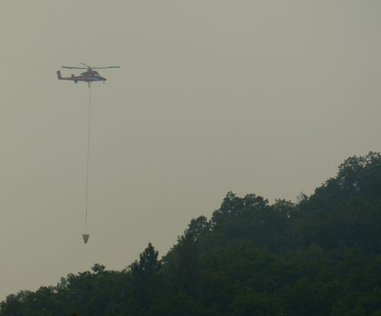 A helicopter was dumping water Thursday on the Hirz Fires north of Redding.