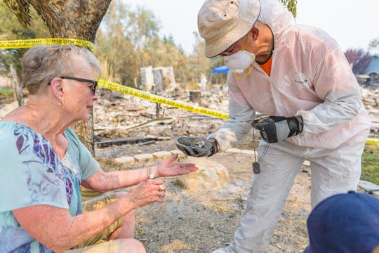 A Samaritan's Purse volunteer hands Charlotte Bailey her dead husband's dog tags, which were found while sifting through the ashes of her home. The Carr Fire destroyed Bailey's home.