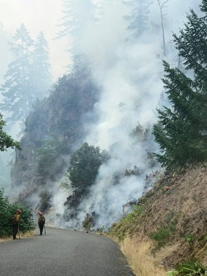 Crews monitor a fire line on Bear Camp Road.