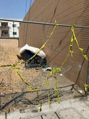 Police tape remains along a fence after a man was shot in Chinatown Thursday.