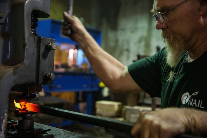 Randy Kiser forges a handle of a skillet in his workshop Thursday, Aug. 2, 2018, at 3Nail Ironware in Paint Rock.
