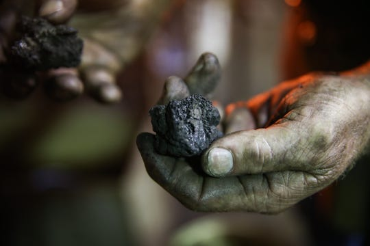 Randy Kiser holds coal from his forge Thursday, Aug. 2, 2018, at 3Nail Ironware in Paint Rock.
