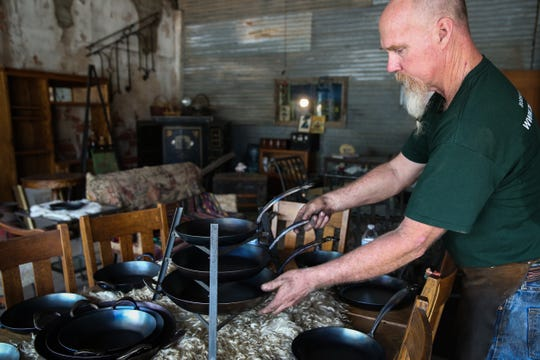 Randy Kiser fixes the display of skillets in his shop Thursday, Aug. 2, 2018, at 3Nail Ironware in Paint Rock.
