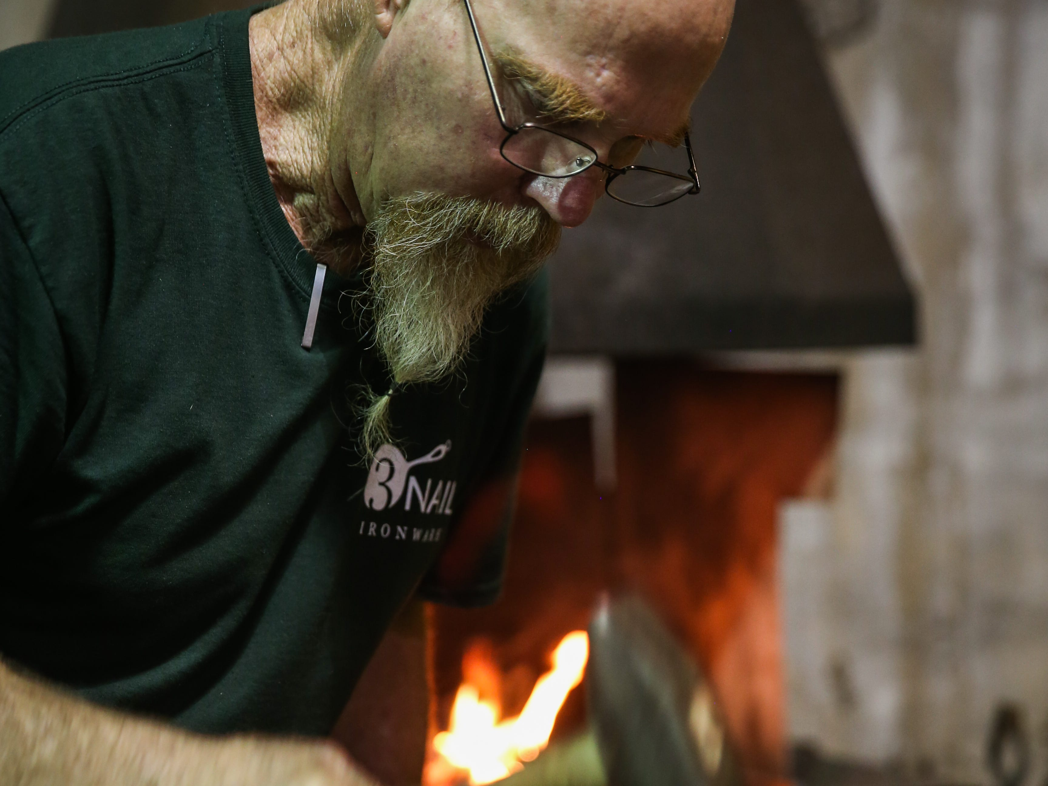 Randy Kiser forges a handle of a skillet in his workshop Thursday, Aug. 2, 2018, at 3Nail Ironwork in Paint Rock.