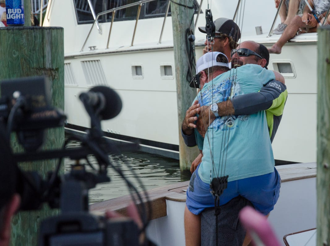 Crew members aboard the Underdog celebrates after their 83 pound White Marlin takes over first place in the category.