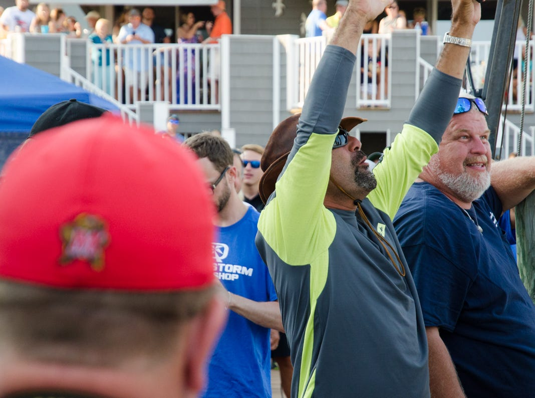 A crew member aboard the Underdog celebrates after their 83 pound White Marlin takes over first place in the category.