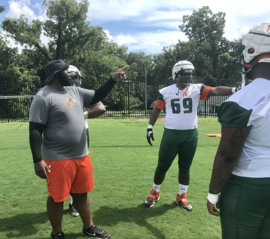 FAMU offensive coordinator/offensive line coach Alex Jackson goes over instructions with players.