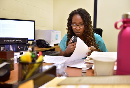 """Dr. Shanedelle Norford, associate medical examiner at the Treasure Coast Medical Examiner's Office, dictates details of the day's autopsy results inside her office on Monday, August 6, 2018, in Fort Pierce. """"It's important to determine cause and manner of death, not only for closure for the family, but for public health as well,"""" Norford said. """"During medical school I realized the hows and the whys were as important as the whats…putting the pieces of the puzzle together."""""""