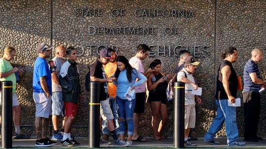 People line up at the California Department of Motor Vehicles prior to opening in Van Nuys on Tuesday.