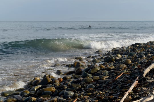 Waves crash on the rocky shore as a surfer waits for a wave at Rincon Beach near the boundary to Santa Barbara County.