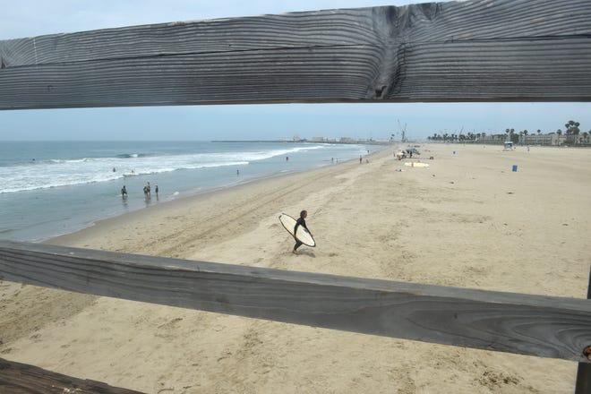 A surfer walks across the sand near the pier at Port Hueneme Beach.