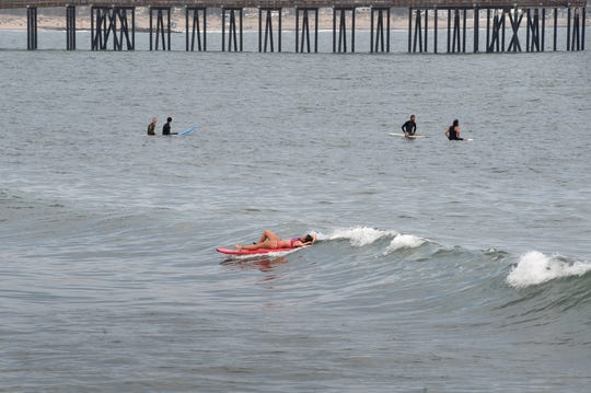 Surfers wait between sets at Surfer's Point near the Ventura Promenade.