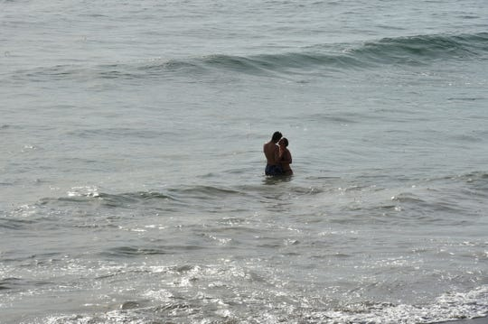 A couple enjoys the water together at Faria Beach.