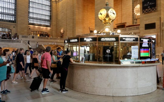 People line up to ask questions of the attendants in the information booth at Grand Central Terminal, Aug. 9, 2018. If you get close enough to one of the two information booths either in the main concourse or in the lower level,  you'll notice the brass structure inside has sliding doors on it. Those open up to reveal a secret connecting staircase between booths.