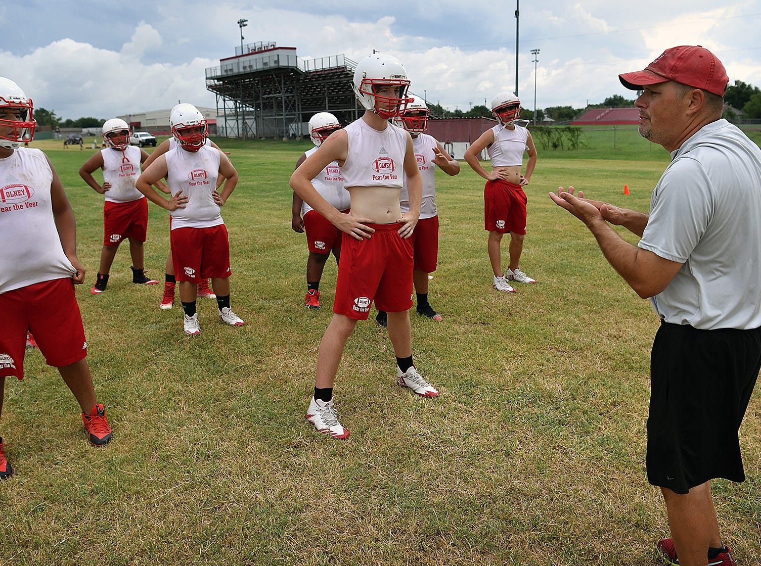 Olney Cubs assistant coach Gunter Rodriguez instructs his offensive linemen as they go through morning workouts Thursday.