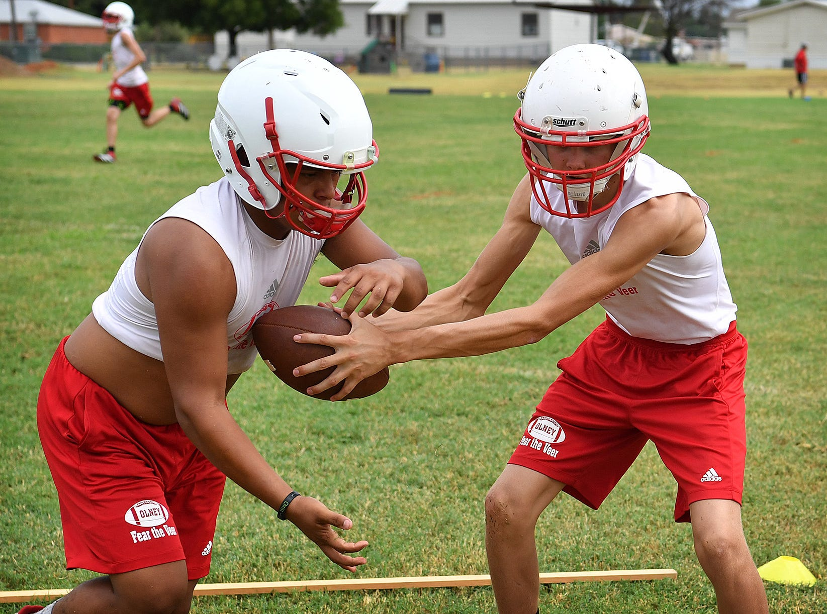 Olney Cubs players work on quick handoffs during the team's morning practices Thursday.