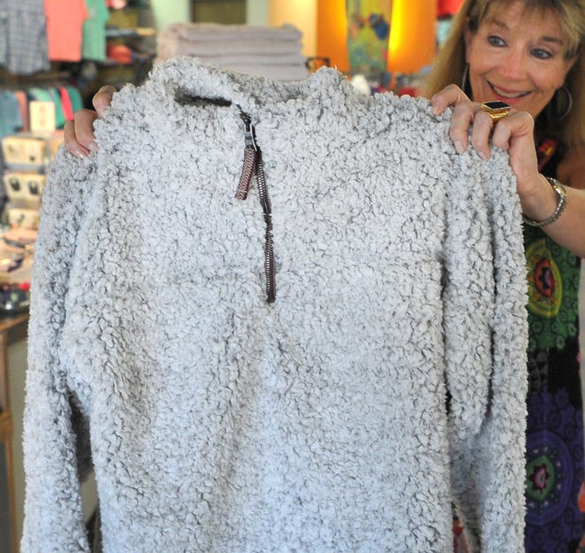 Sales associate Julia Taylor of Annie Jewel & Charlie's, located on Kemp Boulevard, looks at True Grit outerwear Thursday in preparation for the tax-free weekend. The shopping holiday begins on Aug. 10 and ends on Aug. 12, according to the Texas Comptroller website.
