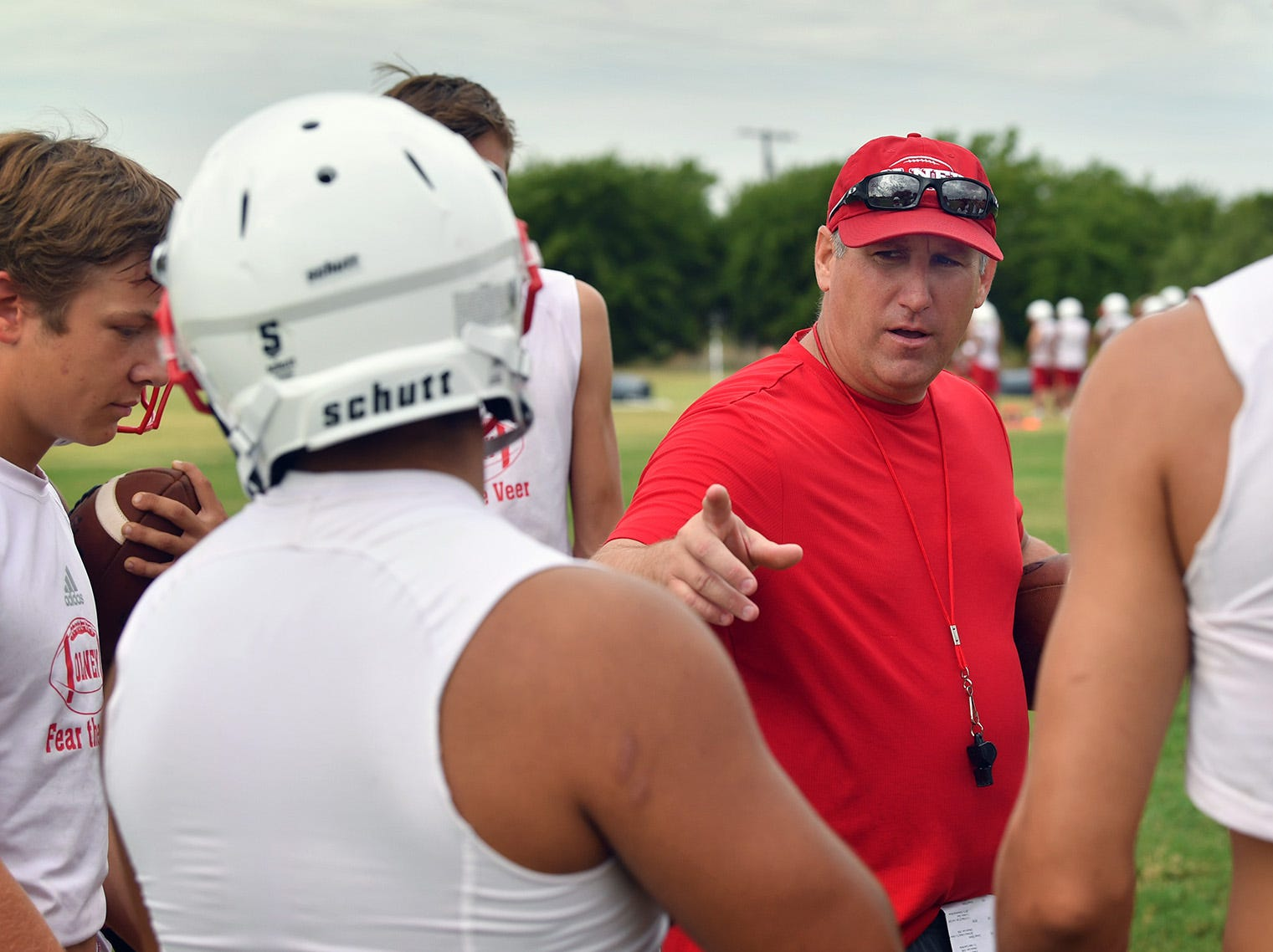Olney Cubs head coach Jody Guy talks with his players between drills Thursday morning. Guy is new to the program and is bringing a new offense with him.