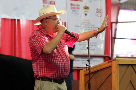 Auctioneer Gary Finley gets the bidding going during the Governor's Blue Ribbon Livestock Auction at the Wisconsin State Fair on Aug. 8.