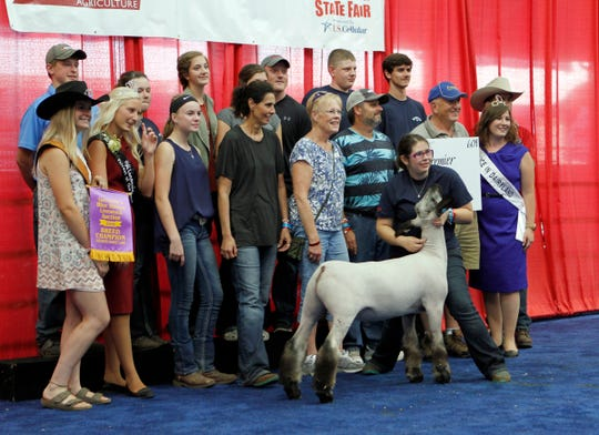 Ainsley Balfanz, of Waterford, poses with her Champion Breed Crossbred Lamb after Premier Insurance Solutions won the bid at the Governor's Blue Ribbon Livestock Auction at the Wisconsin State Fair on Aug. 8.