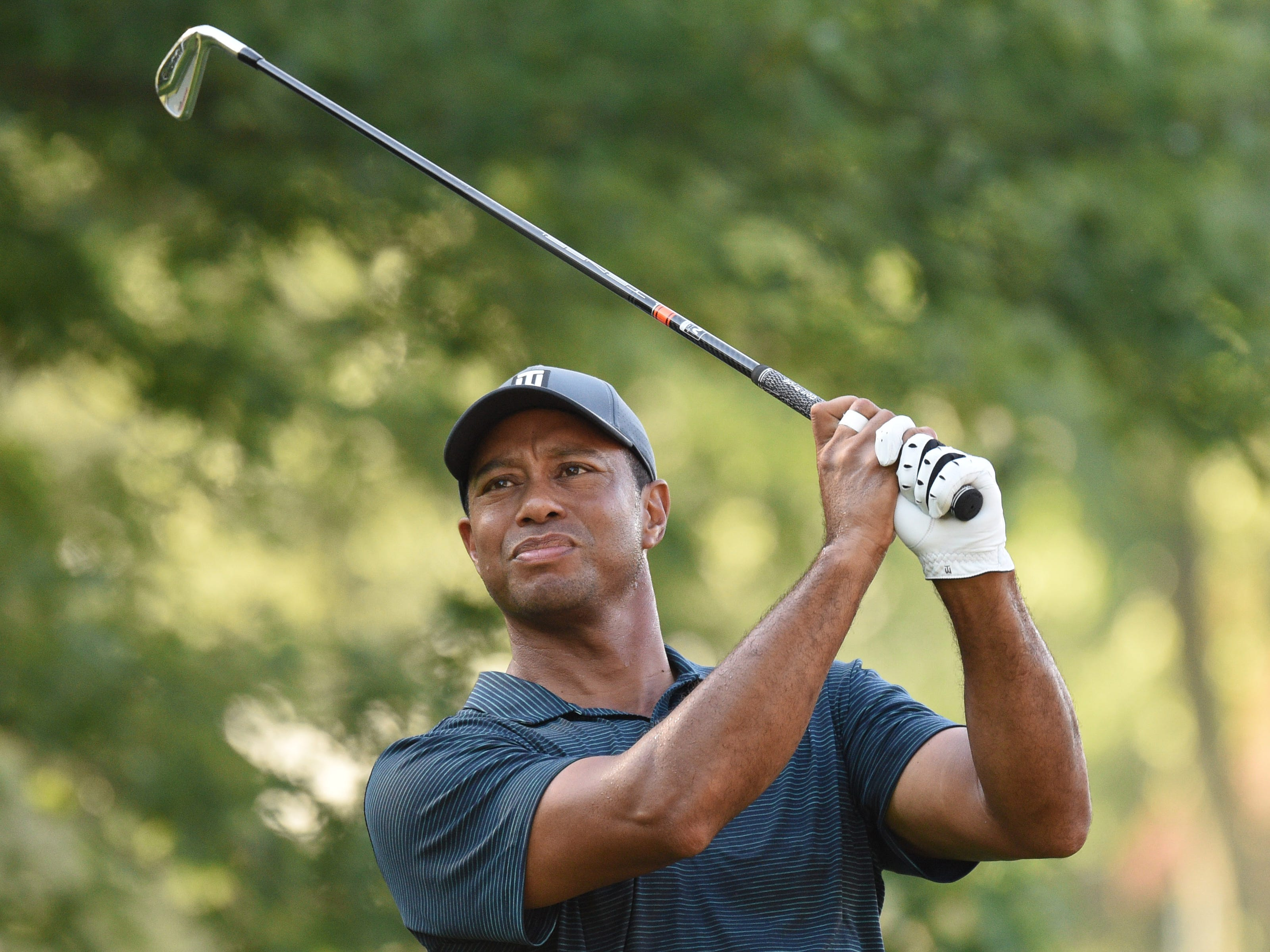 Tiger Woods hits his tee shot on the 11th hole during the first round.