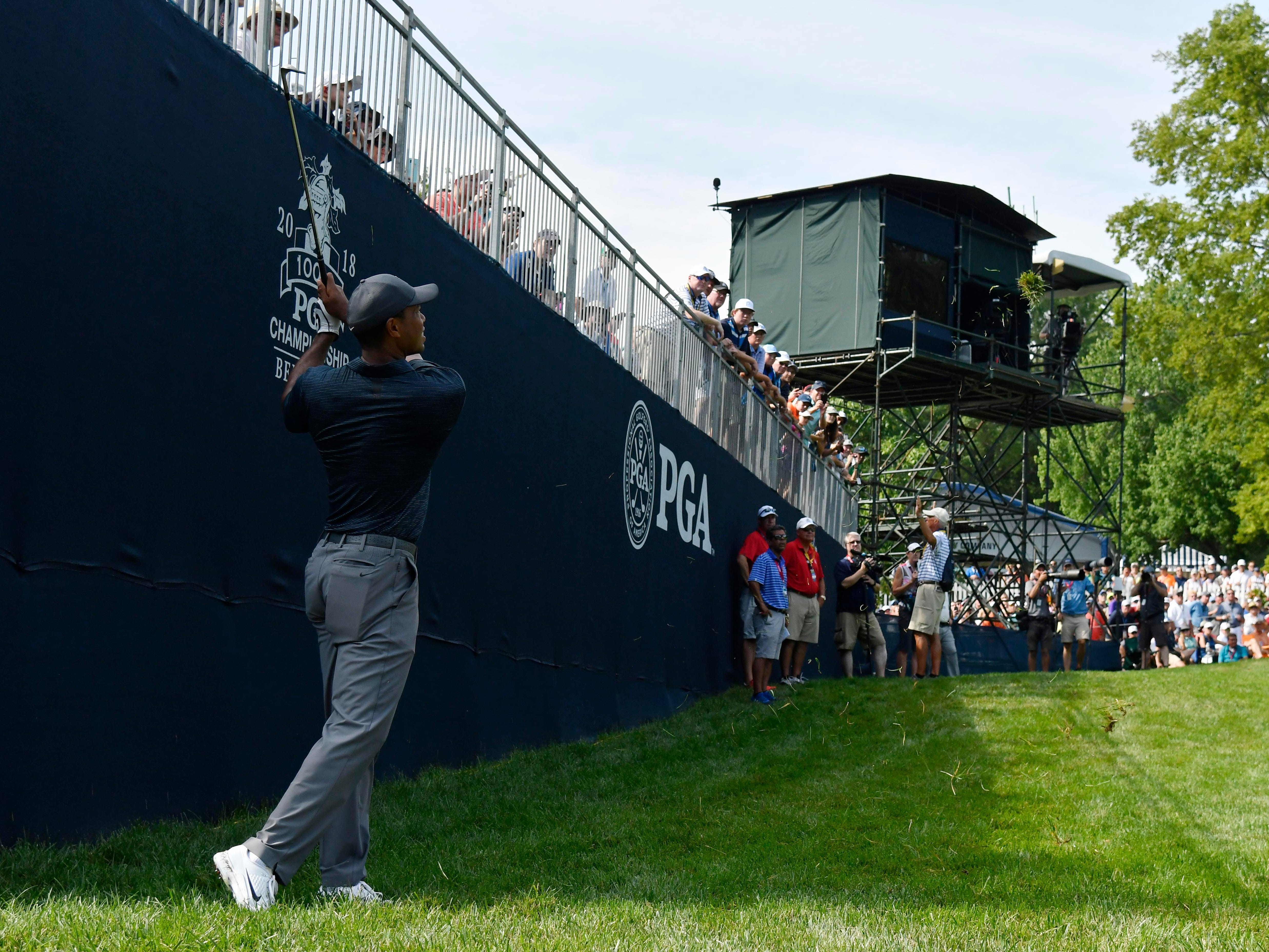 Tiger Woods hits from the rough on the 16th hole.