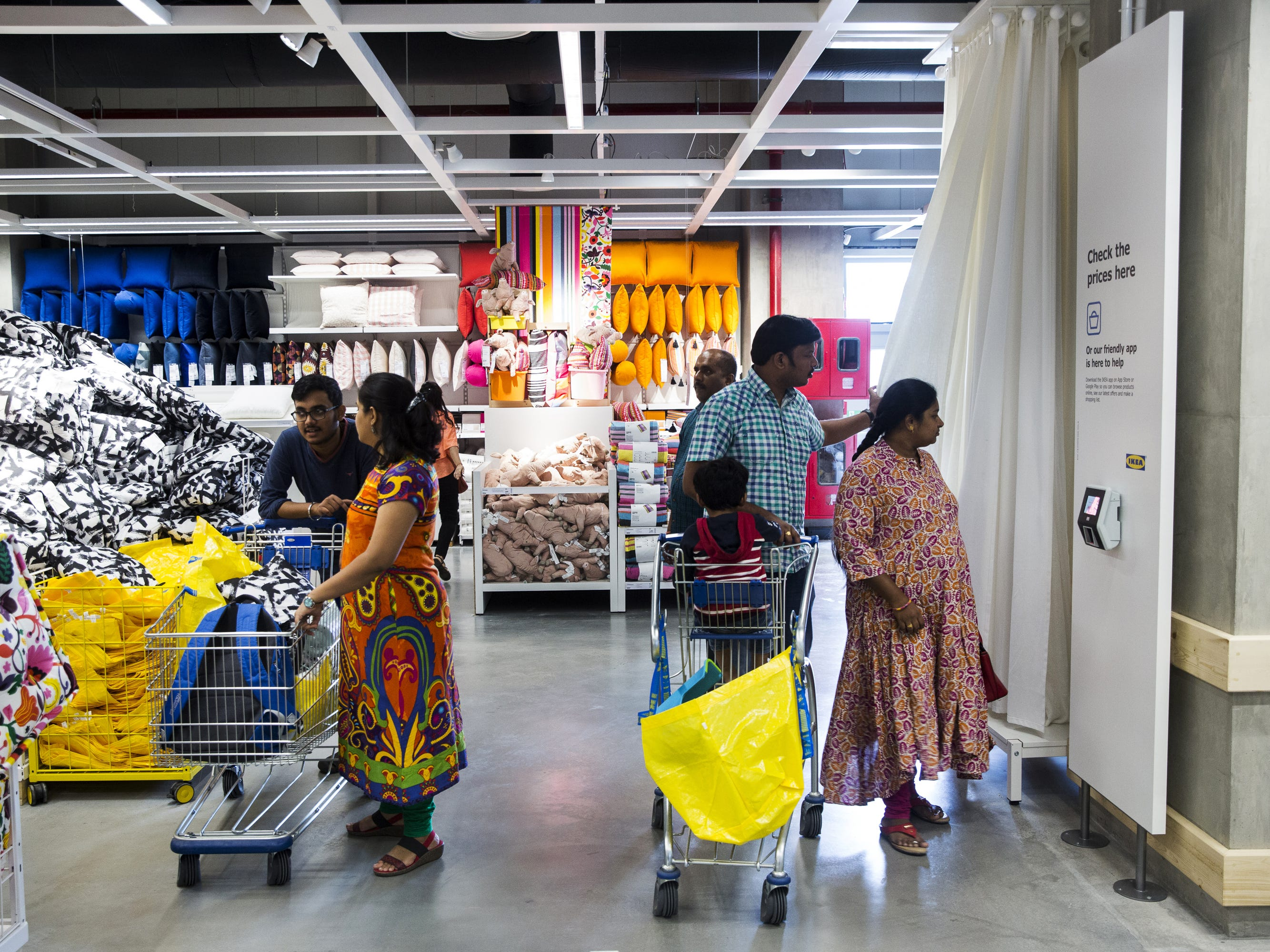 Customers walk past cushions on display inside the Ikea store in Hitech City on the outskirts of Hyderabad, India, on Thursday, Aug. 9, 2018. Ikea's blue-and-yellow stores are instantly recognizable: iconic, monolithic and now, asIndia's first storethrows open its doors to the masses today, operating in more than 400 stores in some 50countries.