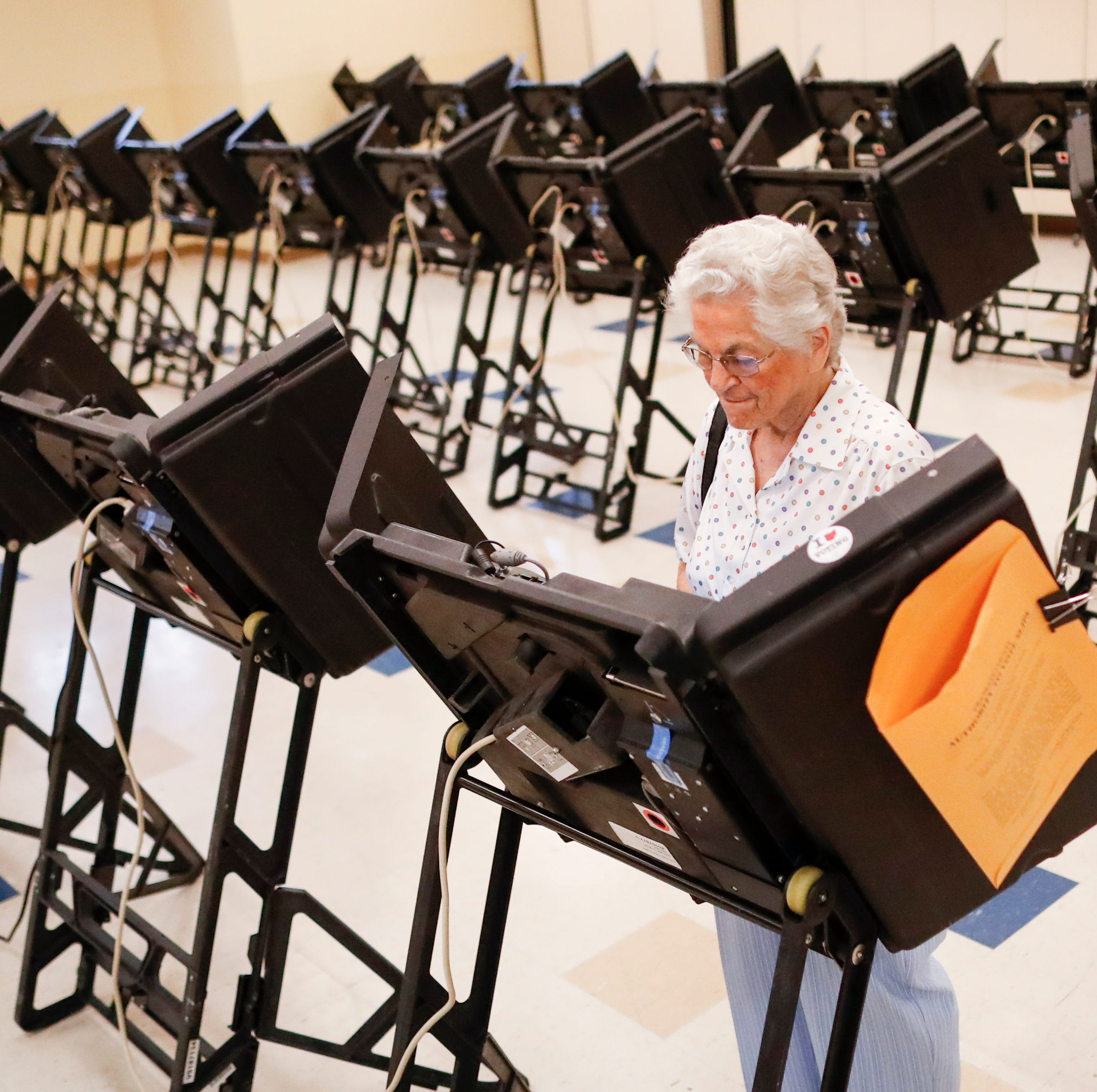 Voters cast their ballots among an array of electronic voting machines in a polling station at the Noor Islamic Cultural Center, Tuesday, Aug. 7, 2018, in Dublin, Ohio.