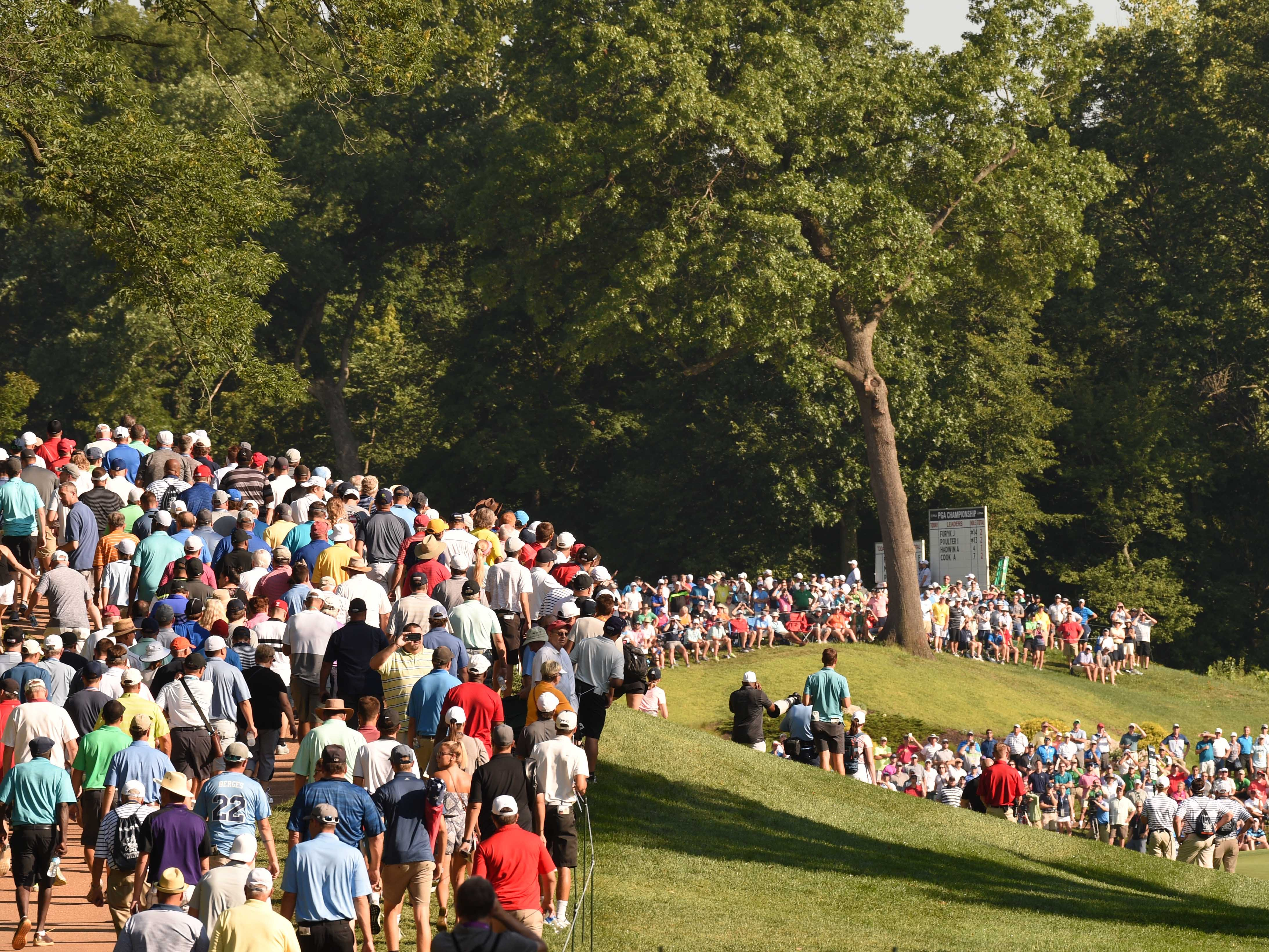 The crowd follows the group of Justin Thomas , Rory McIlroy and Tiger Woods on the 11th fairway during the first round.