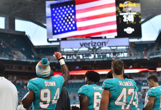 Miami Dolphins defensive end Robert Quinn (94) raises his fist during the national anthem prior to the game against the Tampa Bay Buccaneers at Hard Rock Stadium.